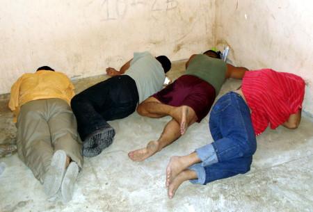 Los polic�as detenidos ocultaron el rostro para no ser fotografiados.