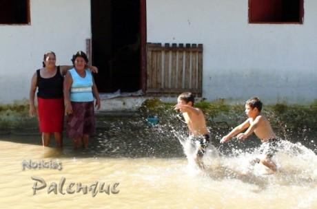 Los niños corretean en la calle inundada mientras las señoras piensan qué comeran.