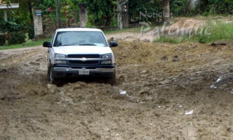 Una camioneta de CFE permanece varada en espera que seque el terreno.